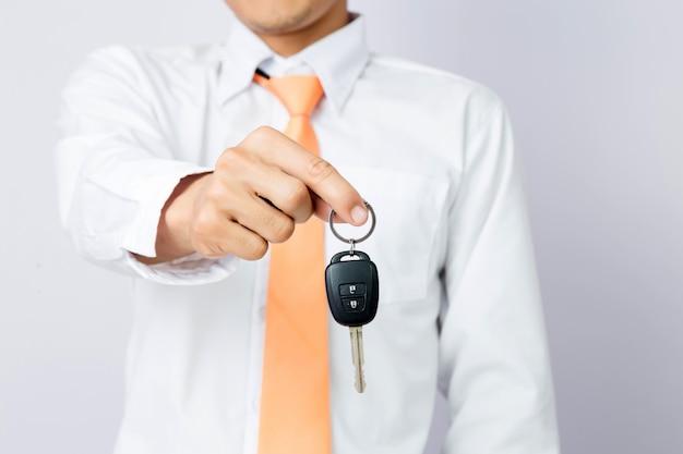 Homme d'affaires en tenant la clé de la voiture, fond isolé