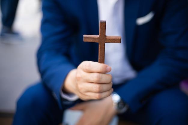 Homme d & # 39; affaires tenant une croix en bois chrétienne
