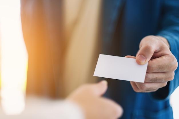 Homme d'affaires tenant et donnant une carte de visite vide