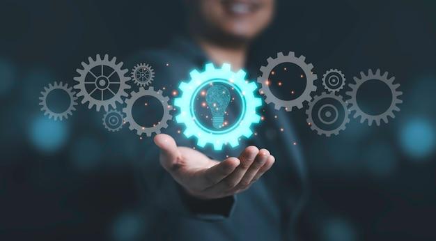 Homme d'affaires tenant un engrenage mécanique bleu avec une ampoule virtuelle pour une idée de pensée créative et un concept d'innovation.
