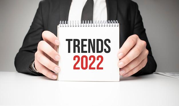 Homme d'affaires tenant une feuille de papier avec un message tendances 2022