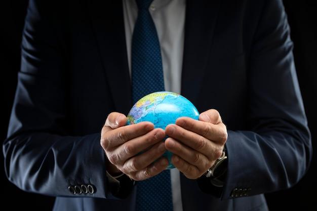 Homme d'affaires tenant un globe dans ses mains sur un fond sombre.