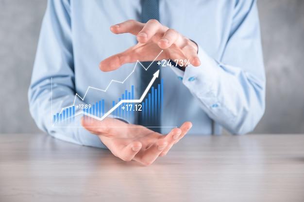Homme d'affaires tenant un graphique avec une croissance positive des bénéfices. planifier la croissance du graphique et l'augmentation des indicateurs positifs du graphique dans son entreprise. plus rentable et en croissance.