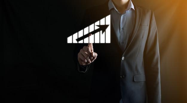 Un homme d'affaires tenant des graphiques holographiques et des statistiques boursières réalise des bénéfices. concept de planification de la croissance et de stratégie commerciale. affichage d'un bon écran numérique de forme économique.