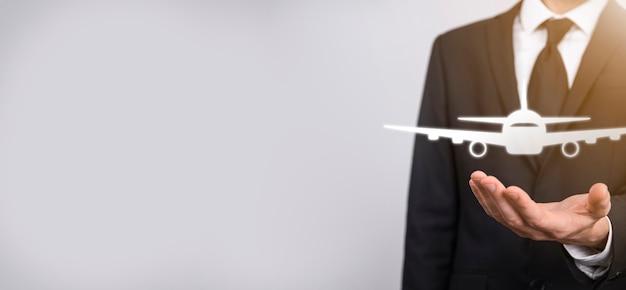 Homme d'affaires tenant une icône d'avion dans ses mains. achat de billets en ligne.voyage.