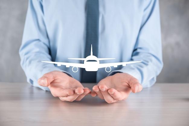 Homme d'affaires tenant une icône d'avion dans ses mains. achat de billets en ligne.