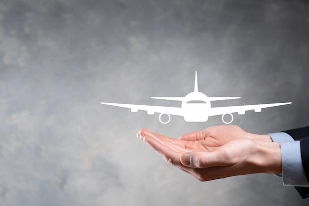 Homme d'affaires tenant une icône d'avion dans ses mains