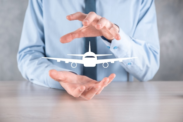 Homme D'affaires Tenant Une Icône D'avion Dans Ses Mains Photo Premium