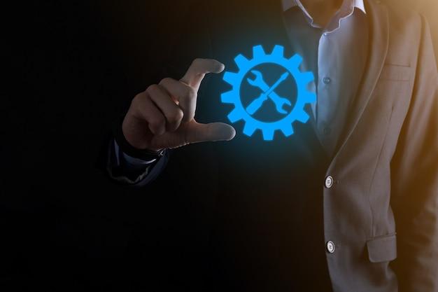 Homme d'affaires tenant l'icône d'engrenage avec des outils. engrenage. concept de diagramme numérique de mise au point cible, interfaces graphiques, écran d'interface utilisateur virtuelle, réseau de connexions.