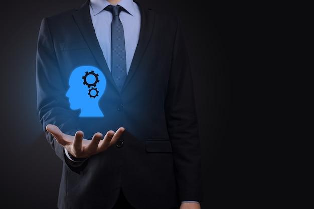 Homme d'affaires tenant une icône d'homme avec des engrenages dans sa tête. intelligence artificielle. la technologie avance. robot. symbole de contour.