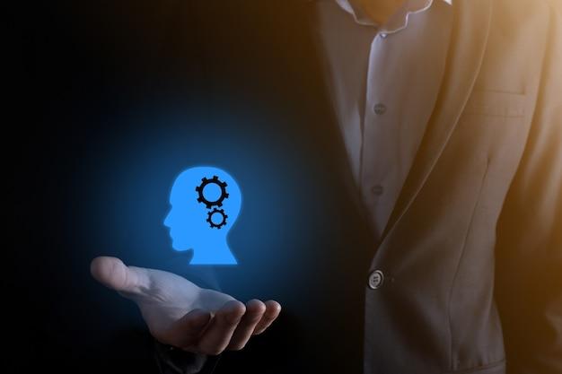 Homme d'affaires tenant une icône d'homme avec des engrenages dans sa tête. intelligence artificielle.