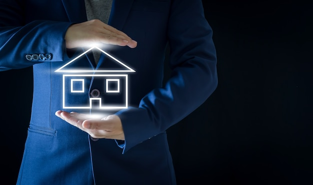 Homme d'affaires tenant l'icône de la maison rougeoyante blanche sur fond noir concepts immobiliers et financiers