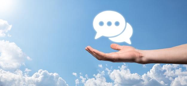 Homme d'affaires tenant une icône de message, signe de notification de conversation de bulle dans ses mains. icône de chat, icône sms, icône de commentaires, bulles de dialogue.