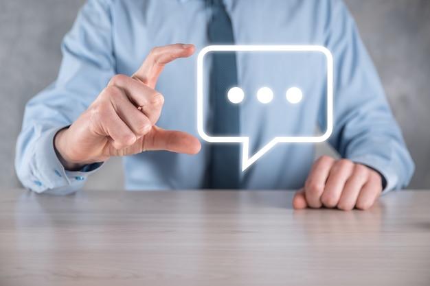 Homme d'affaires tenant une icône de message, signe de notification de conversation de bulle dans ses mains. icône de chat, icône sms, icône de commentaires, bulles de dialogue
