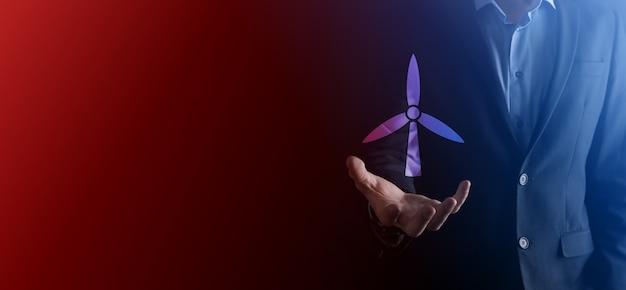 Homme d'affaires tenant une icône d'un moulin à vent qui produit de l'énergie environnementale. fond sombre. rouge néon, lumière bleue.