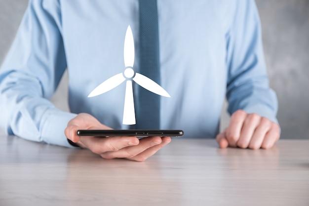 Homme d'affaires tenant une icône d'un moulin à vent qui produit de l'énergie environnementale.