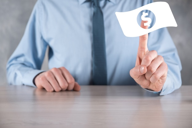Homme d'affaires tenant une icône de pièce d'argent dans ses mains. concept d'argent croissant pour l'investissement et la finance des entreprises. usd ou dollar américain sur un mur de tons sombres.