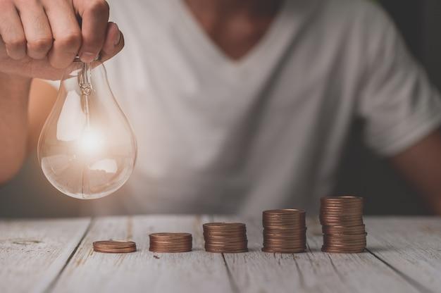 Homme d'affaires tenant une idée de pile d'argent d'ampoule économisant de l'énergie et des finances comptables