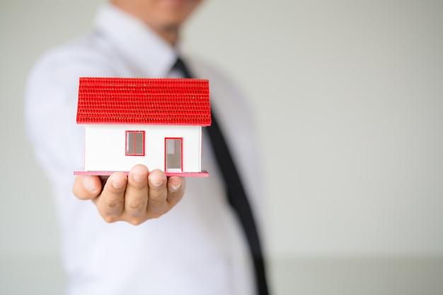 Homme d'affaires tenant la maison modèle