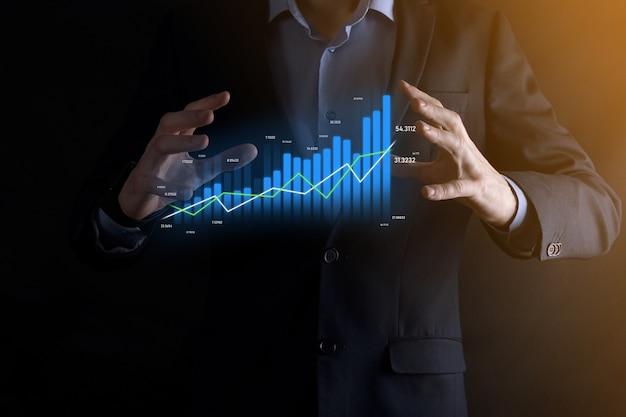 Un homme d'affaires tenant et montrant des graphiques holographiques et des statistiques boursières réalise des bénéfices. concept de planification de la croissance et de stratégie commerciale. affichage d'un bon écran numérique de forme économique.
