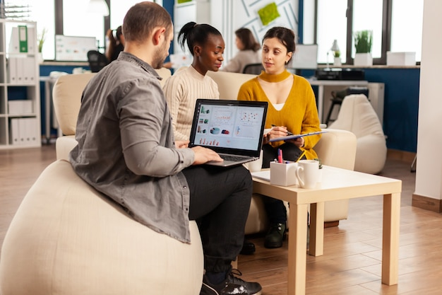 Homme d'affaires tenant un ordinateur portable avec des graphiques financiers tandis que divers employés parlent expliquant le plan de projet examinant les documents assis sur un canapé