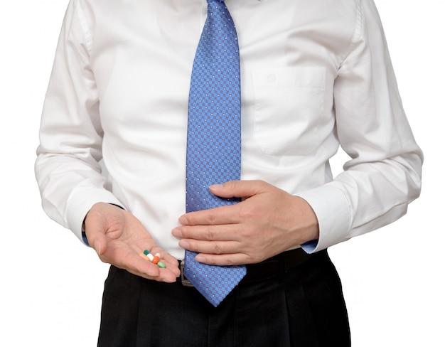 Homme d'affaires tenant la pilule dans la main.