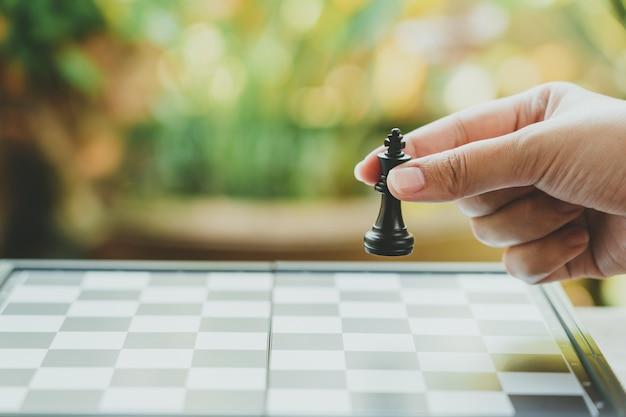 Homme d'affaires tenant un roi d'échecs est placé sur un échiquier.utilisant comme arrière-plan