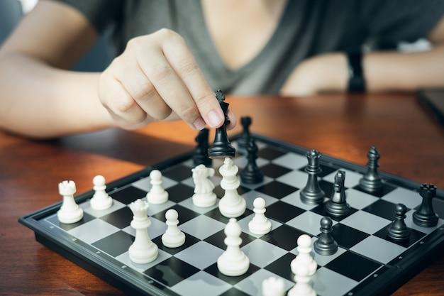 Homme d'affaires tenant un roi d'échecs est placé sur un échiquier.