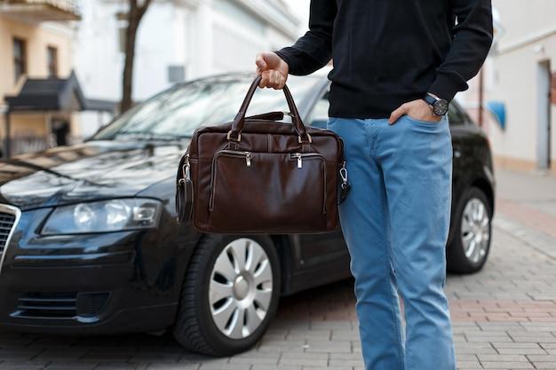 Homme d'affaires tenant un sac en cuir près de la voiture