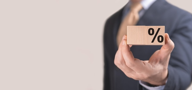 Homme d'affaires tenant un signe de pourcentage dans un cube en bois dans sa main avec espace de copie