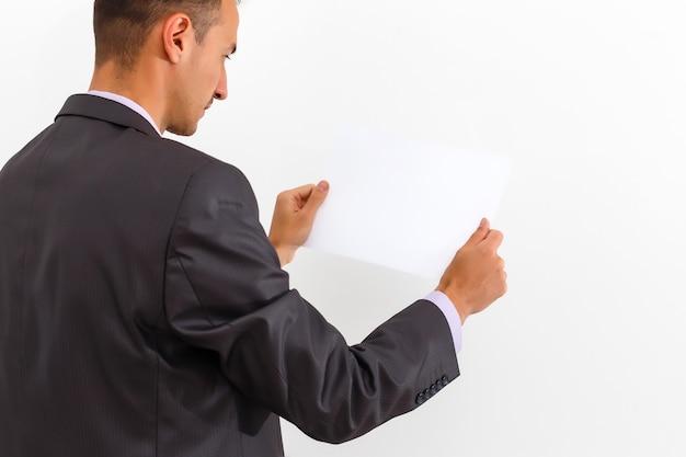 Homme d'affaires tenant un tableau blanc vierge, enseigne, montrant un panneau d'affichage vide sur fond blanc