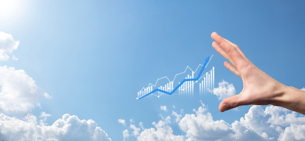 Un homme d'affaires tenant une tablette et affichant des graphiques holographiques et des statistiques boursières gagne des bénéfices. concept de planification de la croissance et de stratégie commerciale. affichage d'un bon écran numérique de forme économique.