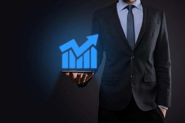 Homme d'affaires tenant une tablette et montrant un hologramme virtuel croissant de statistiques, de graphiques et de graphiques avec flèche vers le haut sur fond sombre. bourse. concept de croissance, de planification et de stratégie de l'entreprise.