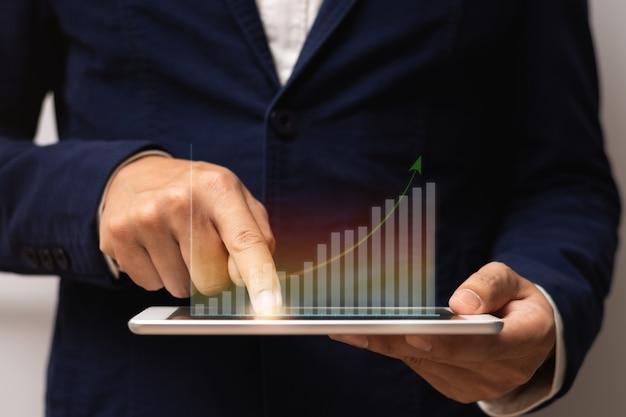Homme d'affaires tenant une tablette et touchez à l'écran avec un graphique de croissance d'hologramme virtuel et une flèche vers le haut