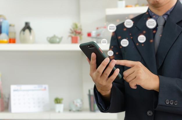 Homme d'affaires tenant un téléphone portable et vérifiant ses e-mails en ligne. smartphone de communication d'entreprise sur un concept de technologie d'interface virtuelle