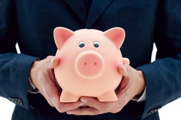 Homme d'affaires tenant une tirelire dans ses mains symbole d'épargne et de bons investissements