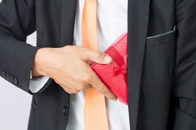 Homme d'affaires tend la boîte cadeau rouge, fond isolé