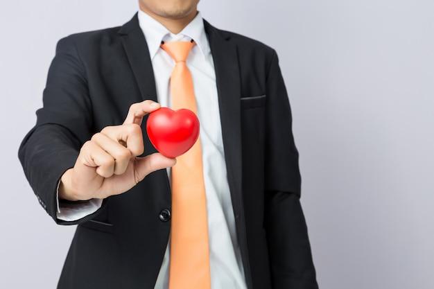 Homme d'affaires tend le coeur rouge, fond isolé