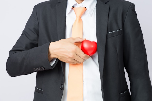 Homme d'affaires tend le coeur rouge