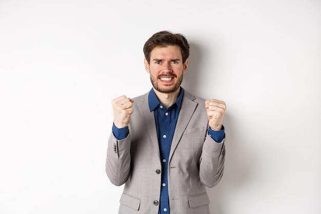 Homme d'affaires tendu se sentir nerveux et sous pression, serrant les poings et les dents, regardant la caméra, gagner de l'argent et avoir l'air inquiet, debout sur fond blanc.