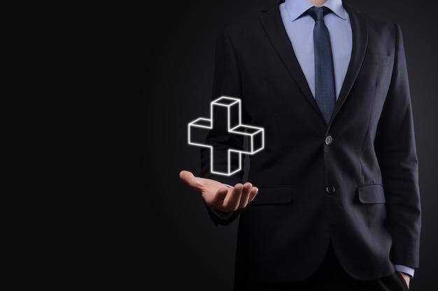 Homme d'affaires tenir l'icône 3d plus, l'homme tenir en main offre une chose positive telle que le profit, les avantages, le développement, la rse représentée par le signe plus.la main montre le signe plus.