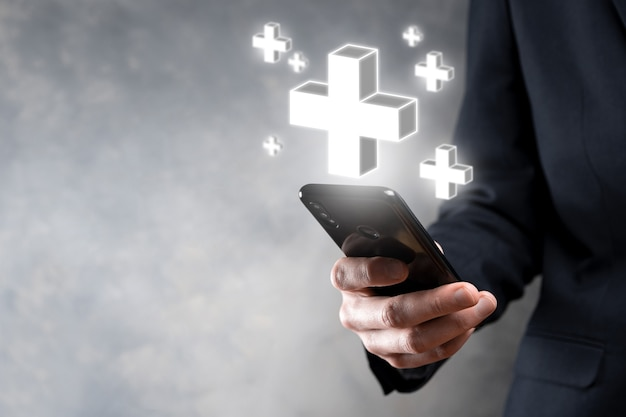 Homme d'affaires tenir l'icône 3d plus, l'homme tenir en main offre une chose positive telle que le profit, les avantages, le développement, la rse représentée par le signe plus