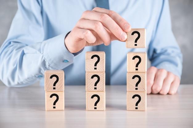Homme d'affaires tenir et mettre en forme de bloc de cube en bois avec des points d'interrogation sur une table grise. espace pour text.concept pour confusion, question ou solution.