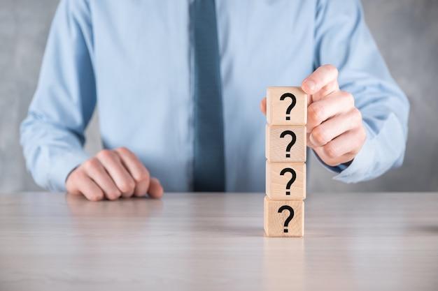 Homme d'affaires tenir et mettre la forme de bloc de cube en bois avec des points d'interrogation sur la table grise. espace pour le texte, concept de confusion, question ou solution.