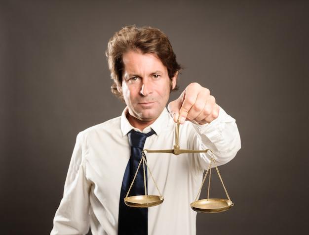 Homme affaires, tenue, a, balance justice, regarder appareil-photo