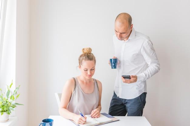 Homme affaires, tenue, calculatrice, et, tasse café, regarder femme, écrire, dans journal