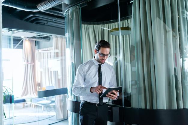 Homme d'affaires en tenue de soirée à l'aide de tablette pour le travail et debout dans le hall. lunettes sur.