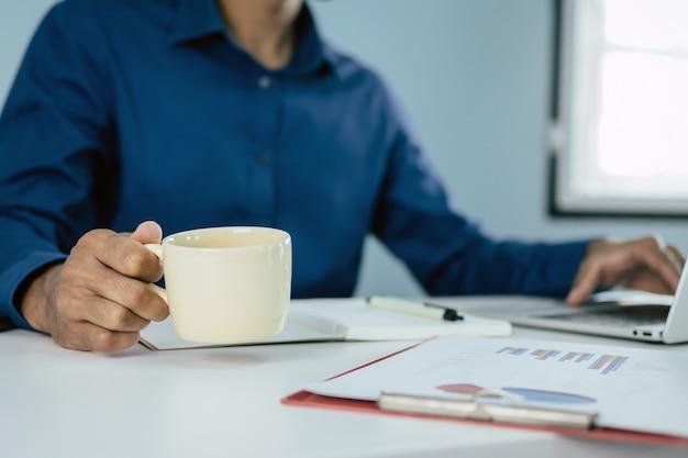 Homme affaires, tenue, tasse à café, travailler, ordinateur, document, rapport, bureau, maison