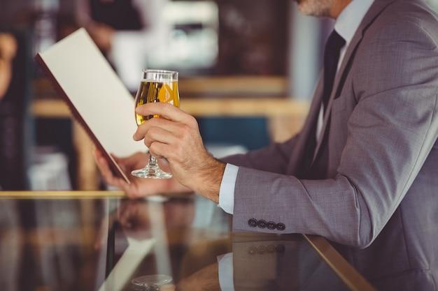 Homme affaires, tenue, verre bière, et, regarder, menu