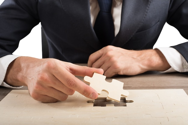 Homme d'affaires terminer un puzzle en insérant la dernière pièce
